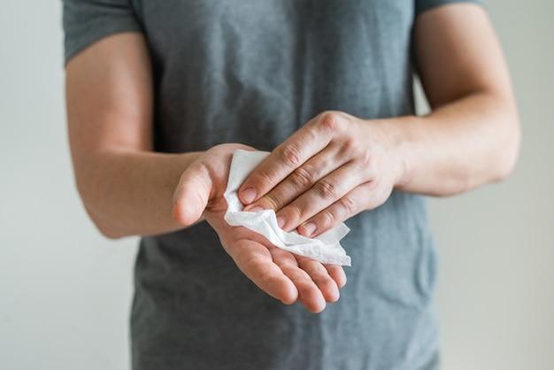 Concetto di protezione della salute dell'epidemia covid-19 con antisettico. mani della lavata della donna facendo uso del tovagliolo antibatterico come misura di prevenzione per coronavirus su fondo blu