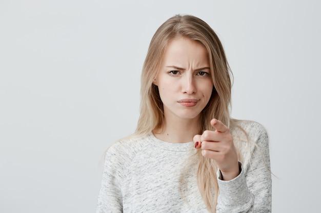 Concetto di pubblicità. donna bionda europea allegra emozionante che indossa le sopracciglia aggrottanti le sopracciglia della maglietta a maniche lunghe e che indica dito indice