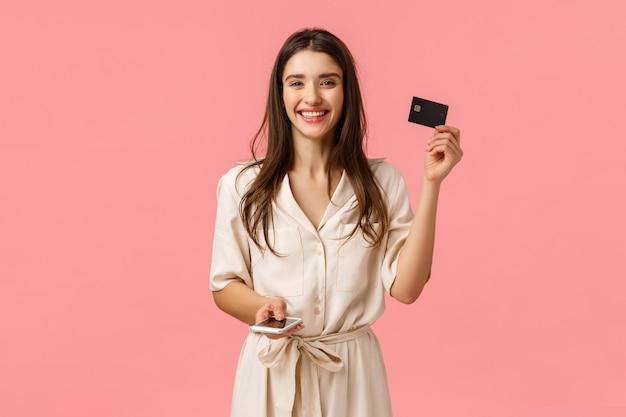Concetto di pubblicità, tecnologia e stile di vita digitale. giovane donna attraente spensierata in vestito splendido che mostra la carta di credito e che tiene telefono, acquisto sorridente online, parete rosa