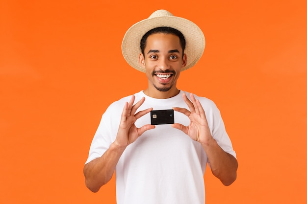 Concetto di pubblicità, vacanze e finanza. tutto ciò di cui hai bisogno è questa banca. ragazzo afroamericano sorridente allegro in cappello di estate, maglietta bianca, tenuta della carta di credito, parete arancio stante