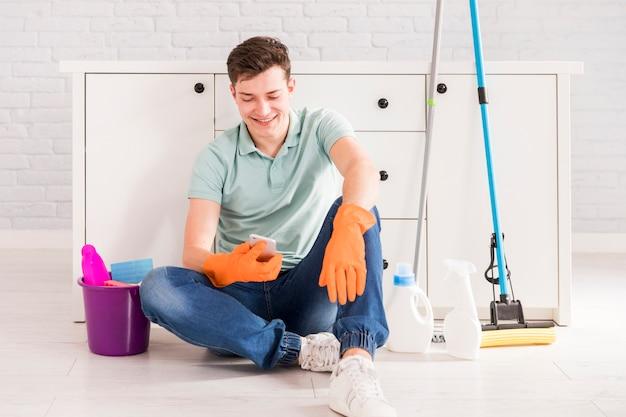 Concetto di pulizia con uomo che tiene smartphone