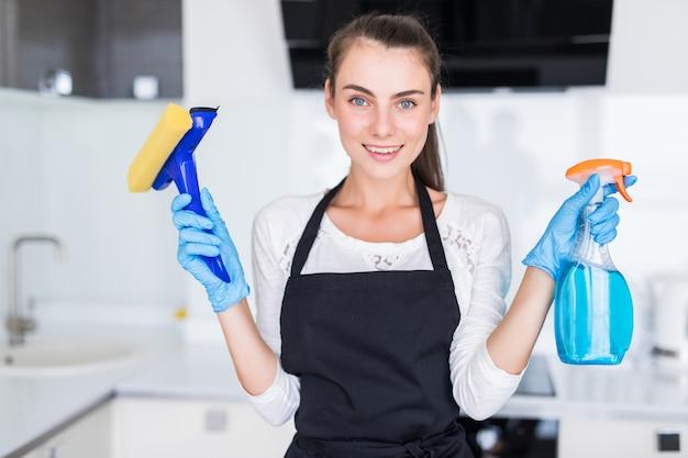 Concetto di pulizia. strumenti di pulizia della tenuta della giovane donna nella cucina