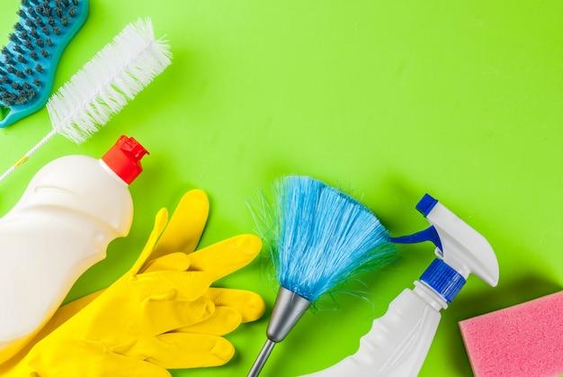 Concetto di pulizie di primavera con forniture, mucchio di prodotti per la pulizia della casa. concetto di lavoretto domestico, sullo spazio verde della copia di vista superiore del fondo