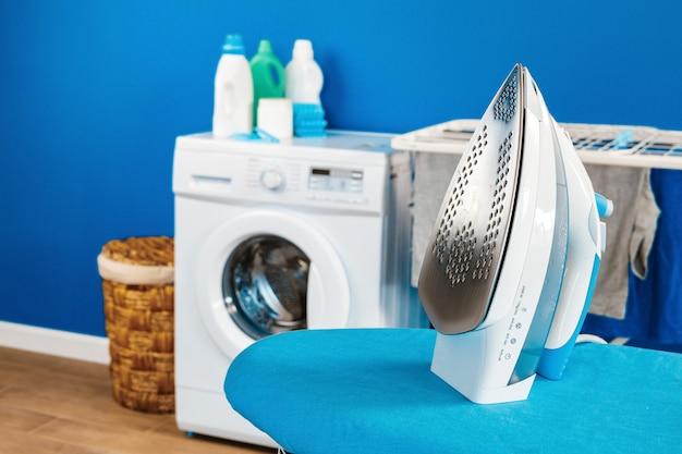 Concetto di pulizie. lavatrice e asse da stiro