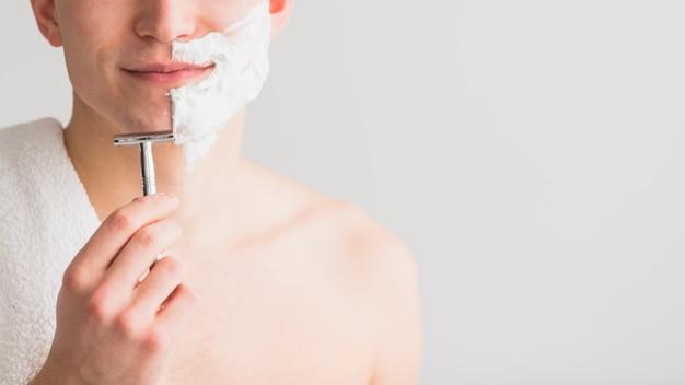 Concetto di rasatura con attraente giovane