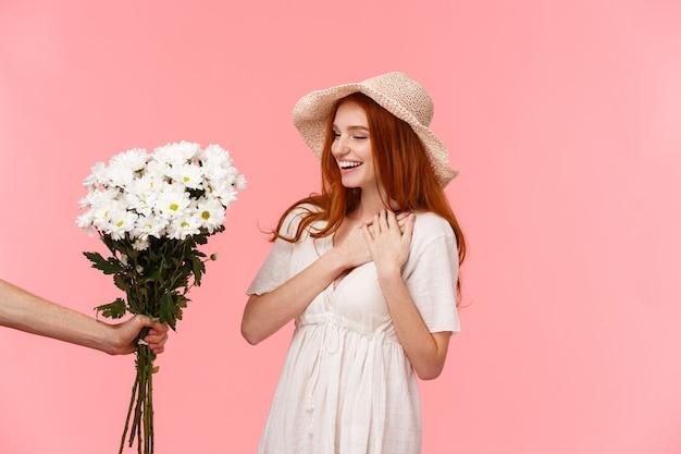 Concetto di regali, celebrazione e tenerezza. sorpresa carina, seducente rossa donna con cappello, abito, incantata con un regalo piacevole, tenendosi per mano sul cuore lusingata, sorridente, guardando bouquet di fiori