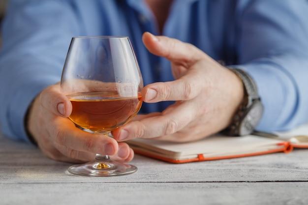Concetto di relax - un bicchiere di brandy in mani maschili. messa a fuoco selettiva.