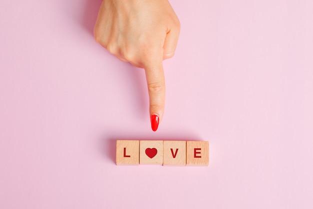 Concetto di relazione piatta laica. dito che mostra cubi di lettere in legno.