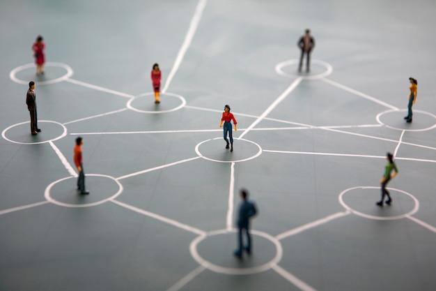 Concetto di rete sociale: persone in miniatura collegate sulla lavagna verde