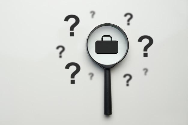 Concetto di ricerca di lavoro - lente d'ingrandimento con custodia e punti interrogativi.