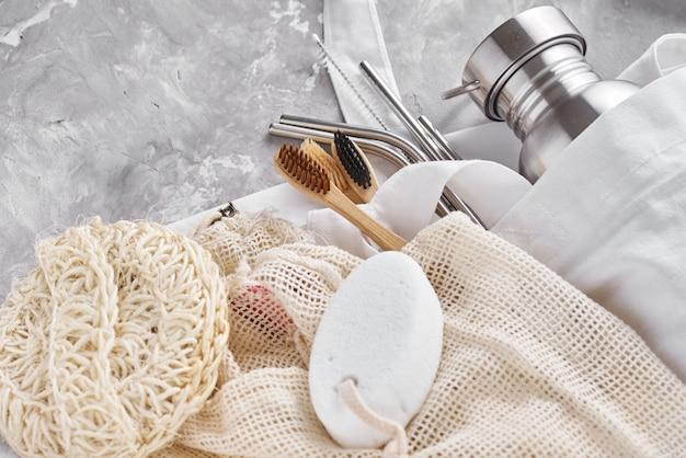 Concetto di rifiuti zero. articoli riutilizzabili ecologici nella borsa della spesa naturale. spazzolini da denti in bambù, spongle, bottiglia in alluminio e tubi metallici