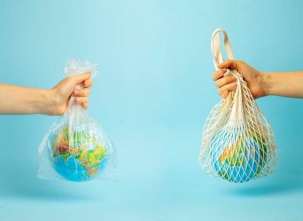 Concetto di rifiuti zero. borsa a tracolla e sacchetto di plastica in una mano femminile con globo terrestre. sacchetti di plastica gratuiti