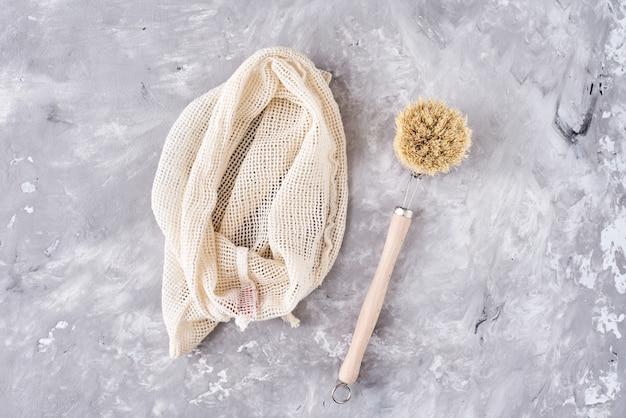 Concetto di rifiuti zero. borsa multiuso e spazzola di legno su grigio.