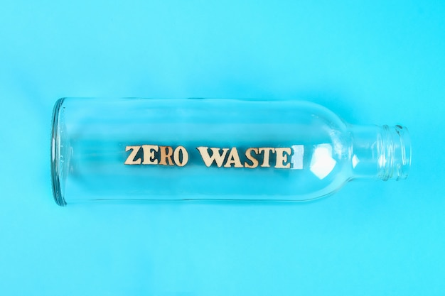 Concetto di rifiuti zero. svuoti la bottiglia di vetro per zero spreco di acquisto e memoria su fondo blu
