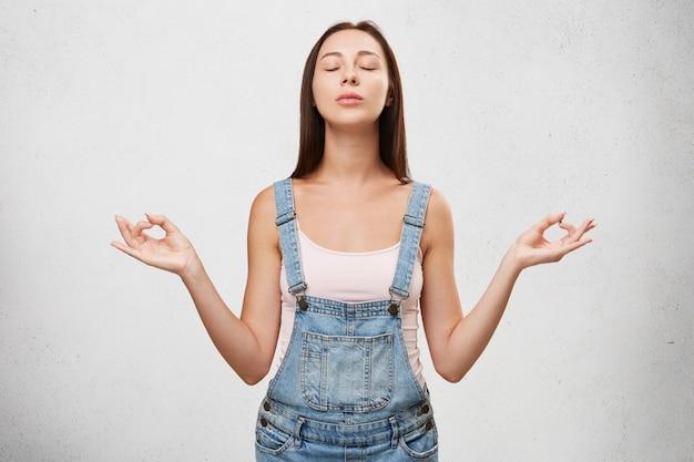 Concetto di rilassamento e meditazione. bella giovane femmina meditando con gli occhi chiusi dopo la pratica dello yoga al mattino, rilassa il corpo e schiarisce la mente, preparandosi per il nuovo felice giorno