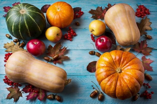 Concetto di ringraziamento con zucche e foglie su fondo di legno blu