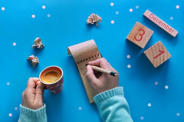 Concetto di risoluzioni del nuovo anno, mano con caffè, taccuino, calendario di legno e caffè sul blu
