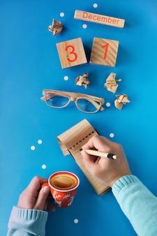 Concetto di risoluzioni del nuovo anno, mano con la penna, taccuino, calendario di legno e caffè sul blu