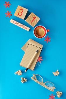 Concetto di risoluzioni del nuovo anno. taccuino, occhiali, calendario in legno e caffè sul blu