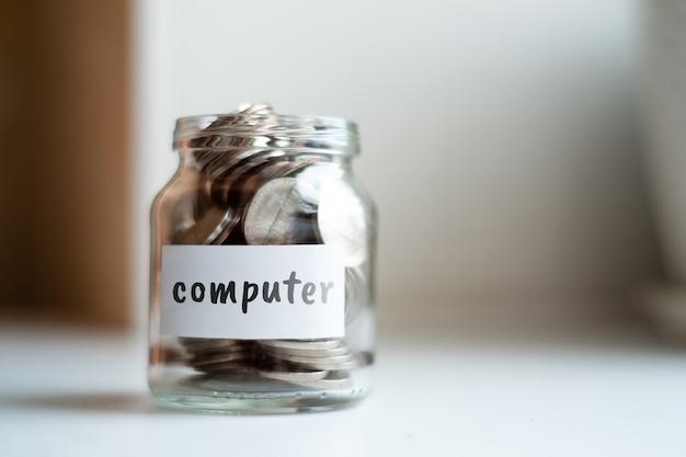 Concetto di risparmio per computer - vaso di vetro con monete e iscrizione.