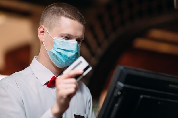 Concetto di ristorante, persone e servizio. uomo o cameriere in maschera medica al bancone con cassa lavorando al bar o alla caffetteria.