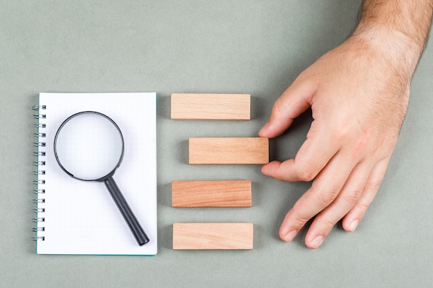 Concetto di risultati di ricerca e ricerca con il taccuino, lente, blocchi di legno sulla vista superiore del fondo grigio. raccolta a mano di uno dei risultati. immagine orizzontale