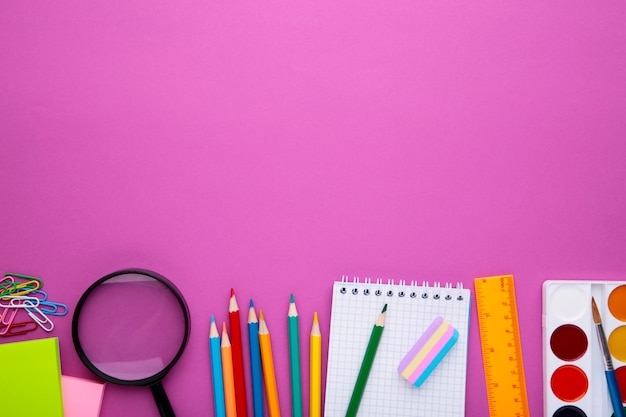 Concetto di ritorno a scuola. rifornimenti di scuola su fondo rosa, vista superiore