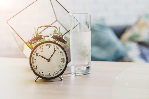 Concetto di salute dell'acqua potabile. sveglia e bicchiere d'acqua sulla tavola