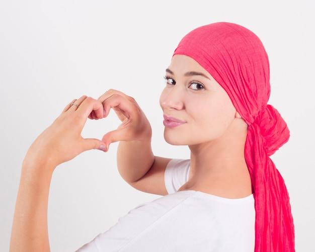 Concetto di salute, della medicina e del cancro al seno - donna che fa gesto del cuore con le mani