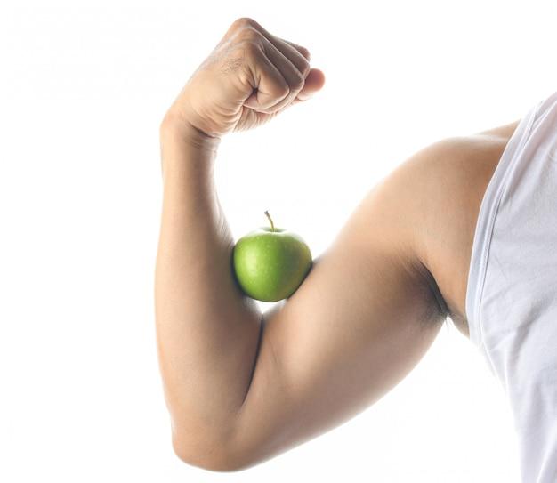 Concetto di salute, mela verde e muscolo del braccio su fondo bianco.