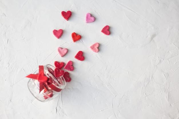 Concetto di san valentino. barattolo con cuori di dolci su uno sfondo chiaro, vista dall'alto