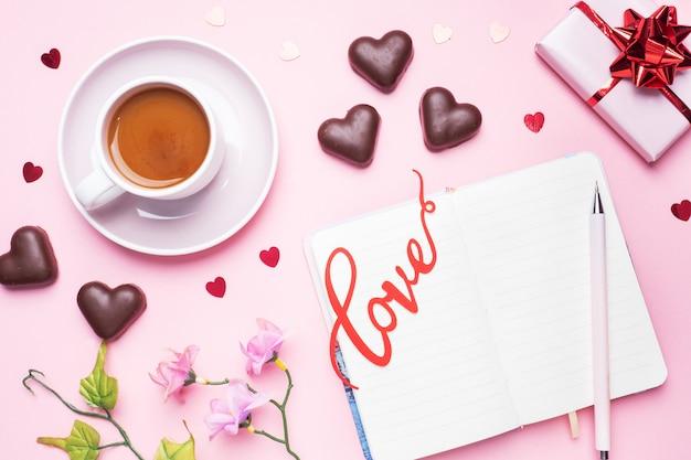 Concetto di san valentino. caramelle e caffè al cioccolato, cuori su uno sfondo rosa. spazio piatto per la copia. biglietto d'auguri e regalo.