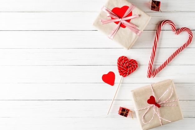 Concetto di san valentino. caramelle e contenitori di regalo a forma di cuore su di legno bianco