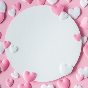 Concetto di san valentino. cartolina d'auguri con cuori rosa e bianchi e spazio per testo. vista dall'alto. disteso. avvicinamento.