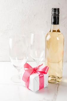 Concetto di san valentino con vino, bicchieri e piccolo regalo