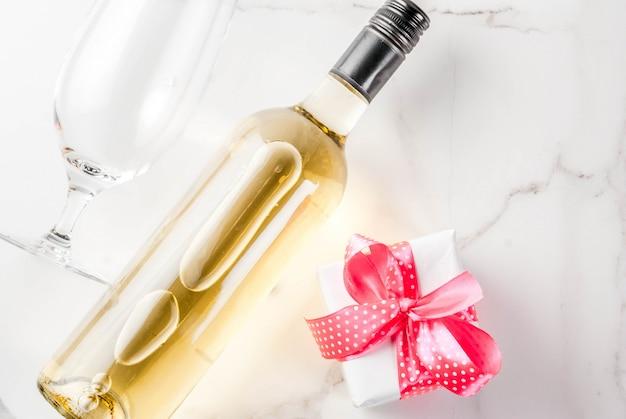 Concetto di san valentino con vino, due bicchieri e confezione regalo