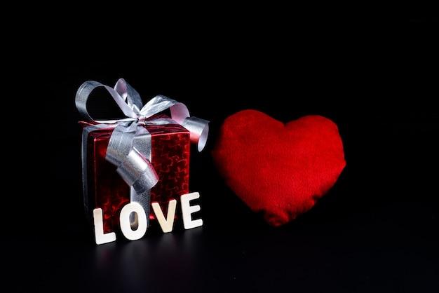 Concetto di san valentino confezione regalo, forma cuore e lettere in legno parola
