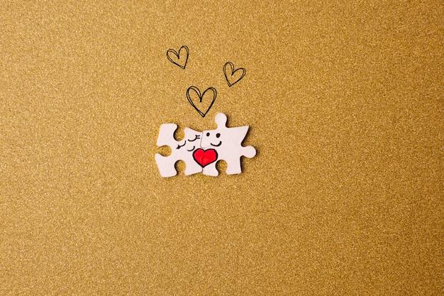 Concetto di san valentino. coppia di puzzle con cuori su uno sfondo d'oro.
