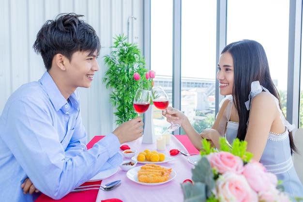 Concetto di san valentino, giovani coppie asiatiche felici che hanno romantico il pranzo con tintinnio che tosta i bicchieri di vino al ristorante.