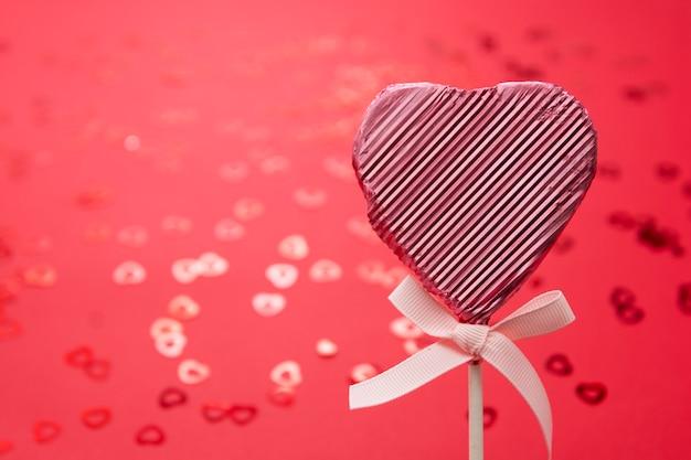 Concetto di san valentino, lecca-lecca rosa a forma di cuore isolata su fondo rosso, con il bokeh dei coriandoli, spazio della copia.