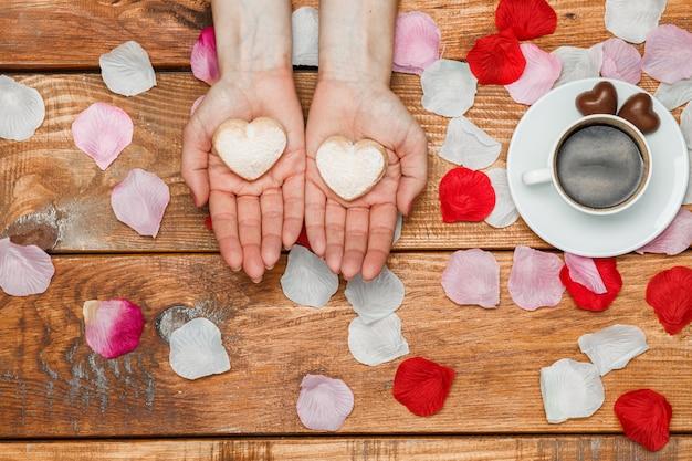 Concetto di san valentino. mani femminili con cuori su legno con petali di fiori e tazza di caffè