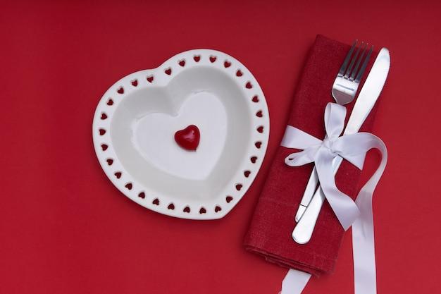 Concetto di san valentino. piatto bianco a forma di cuore e posate d'argento