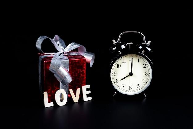 Concetto di san valentino sveglia con scatola regalo e lettere in legno parola