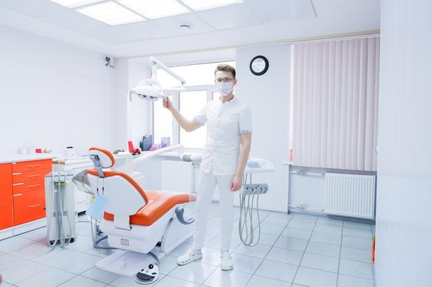 Concetto di sanità, di professione, di stomatologia e della medicina - dentista invecchiato mezzo maschio in maschera protettiva sopra l'ufficio medico