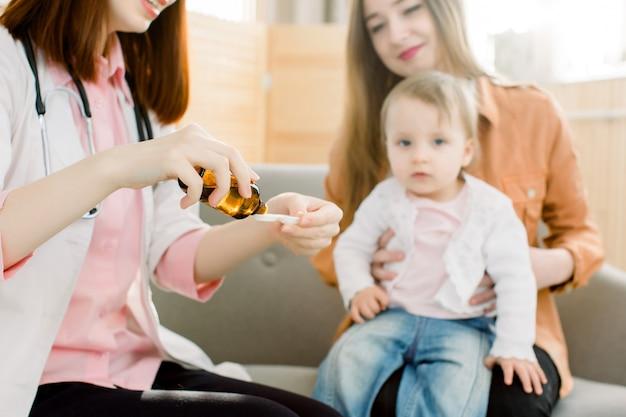 Concetto di sanità e medicina. farmaco di versamento della mano della donna o sciroppo antipiretico dalla bottiglia al cucchiaio. piccola neonata e madre graziosa che si siedono sul sofà sui precedenti