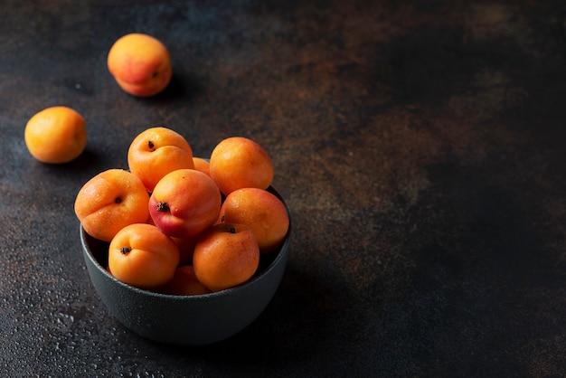Concetto di sano cibo vegano con albicocche dolci in uno sfondo scuro,