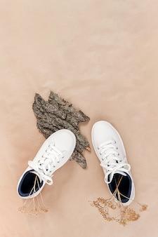 Concetto di scarpe etiche vegetariane. un paio di sneaker bianche con fiori secchi su corteccia d'albero e muschio, carta artigianale neutra