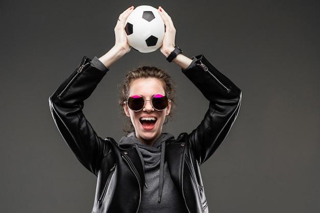 Concetto di scommesse sportive. ragazza in una giacca di pelle e felpa grigia con gli occhiali tiene la palla sopra la testa su grigio scuro