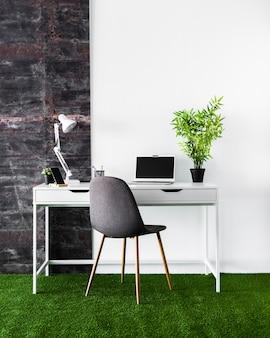 Concetto di scrivania con computer portatile bianco
