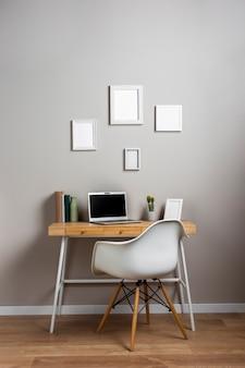 Concetto di scrivania con sedia bianca e portatile